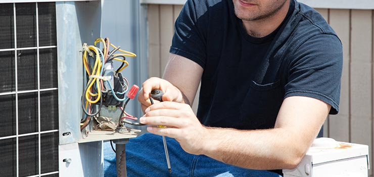 A technician is inspecting the wires of an outdoor air conditioning unit.