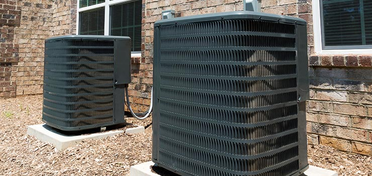Two large outdoor air conditioning units on cement platforms.