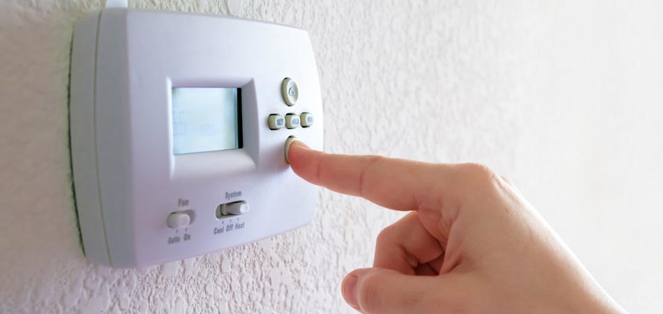 A person adjusting their thermostat to reduce the temperature.