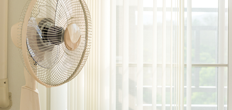 A white fan in front of a sunlit window that is covered with transparent yellow curtains.