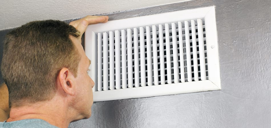 A man is inspecting the air ducts before determining if they need cleaning.