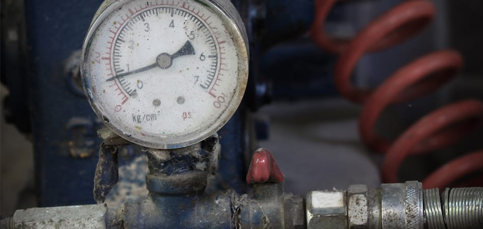 A pressure gauge on an old boiler that shows signs of needing replacement.