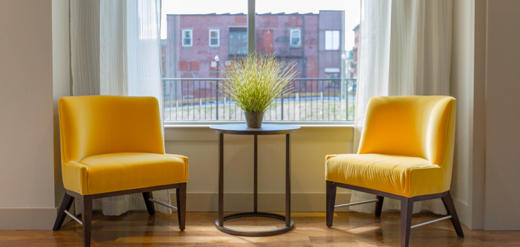 two yellow chairs near window