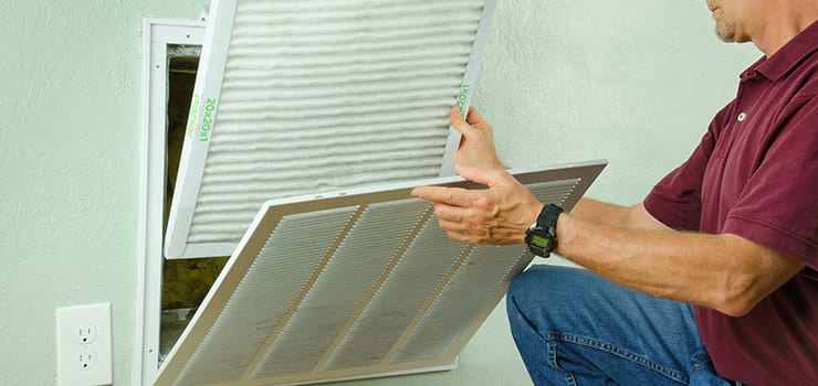 Changing the air filter for increased indoor air quality.