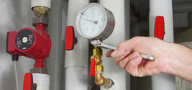 A furnace installation technician is installing a pressure gauge.
