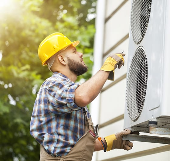 A technician is inspecting the fans of a residential HVAC system.